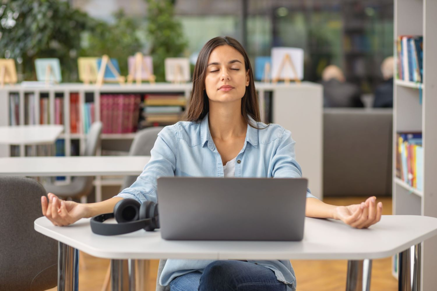 Woman in blue jeans and chambray shirt at desk with laptop and headphones, calmly practising desk yoga
